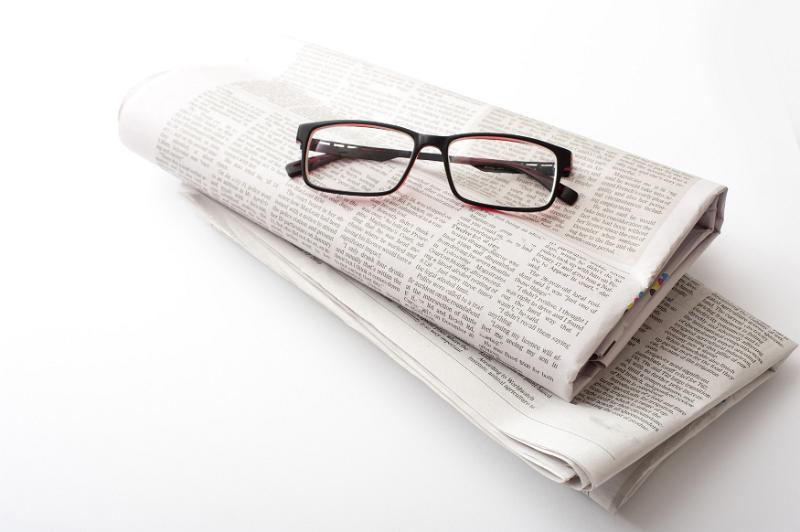 Pair Of Generic Reading Glasses On Two Folded Newspapers Over A White Background With Copy Space Arranged Diagonally